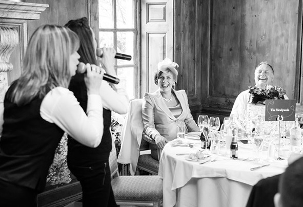 Two singing waitresses serenading the bride and groom.