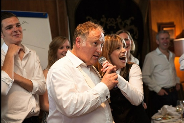 A singing waitress singing with a guest.