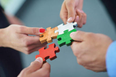 hands holding wooden puzzle pieces