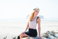 High School Senior portrait on the Oregon coast she has blonde hair and is sitting on a log in the sand