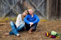 engagement session in Estacada Oregon bride and her fiance sit in front of a barn he has red hair and she wears a lacy top