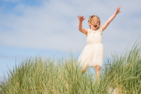 family session portrait of a little girl with blonde hair and yellow dress jumps over a sand dune she leaps in the air with her arms reaching towards the sky through long green grass