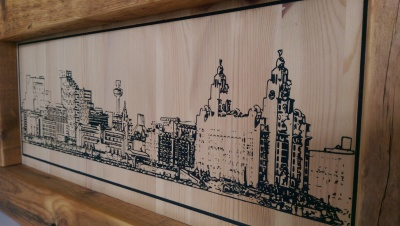 Liverpool skyline laser engraved into reclaimed wood and hand painted.