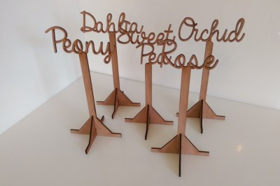 Laser cut wooden custom table name stands.
