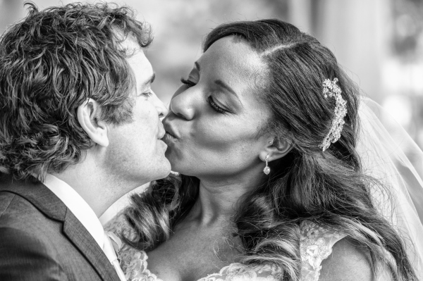 bride and groom kissing each other in church , cheltenham wedding photographer
