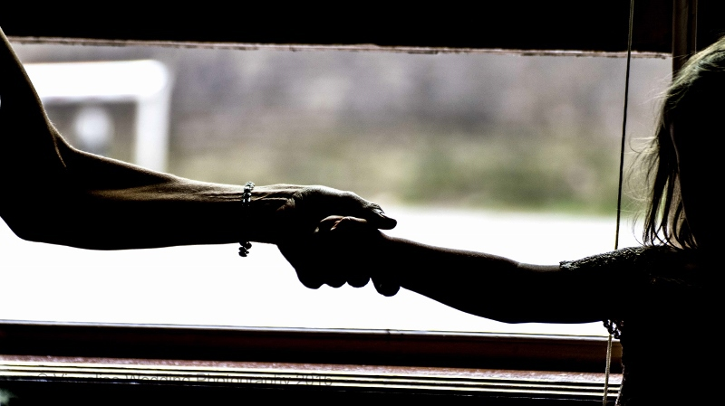 CASWELL HOUSE WEDDING PHOTOGRAPHER mum and girl holding hands looking out of a window.