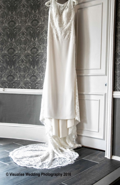 BURFORD wedding photography an ivory wedding dress hanging on a door