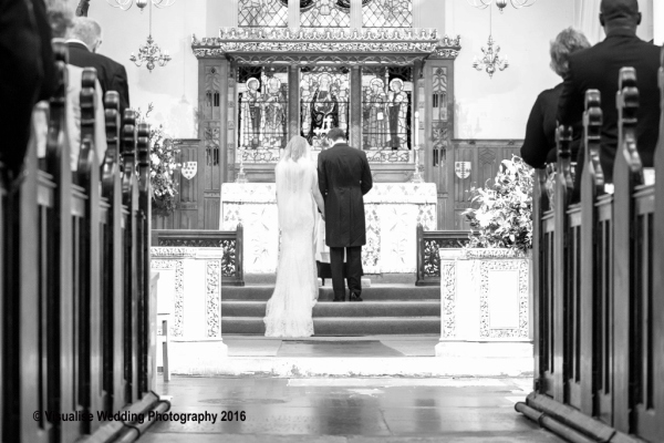 bride and groom kneeling at the altar