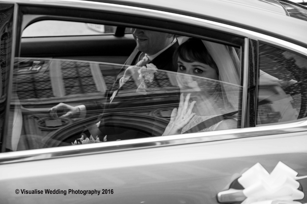 bride leaving in the wedding car waving