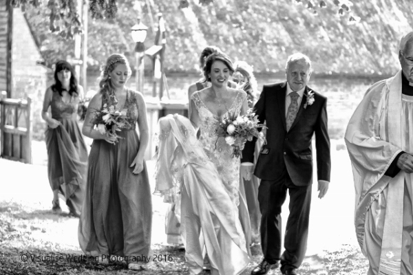 Oxfordshire Wedding Photographer the bride and bridesmaids walking to the church with the father of the bride.