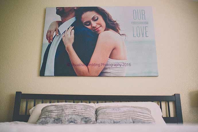 a canvas print hanging above a bed of a woman holding aman close