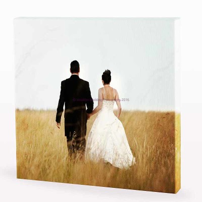a canvas print of a couple walking through a field