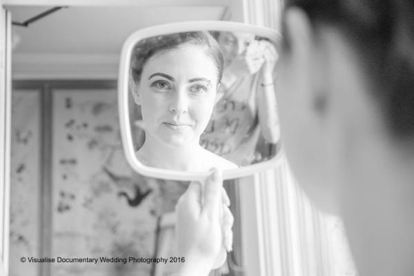 bride looking into a mirror at the camera