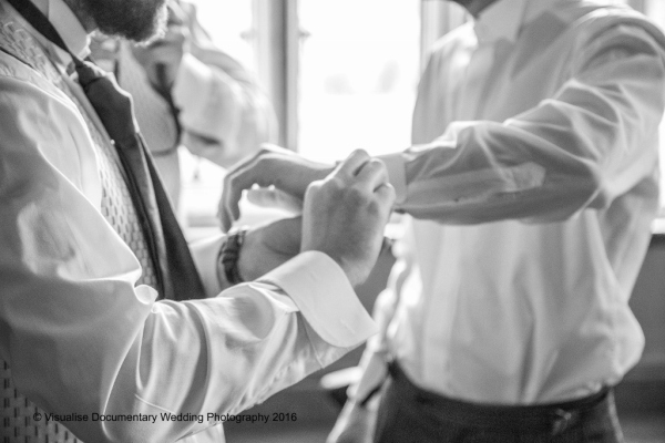 groom and groomsmen putting on cuff links at wedding venue
