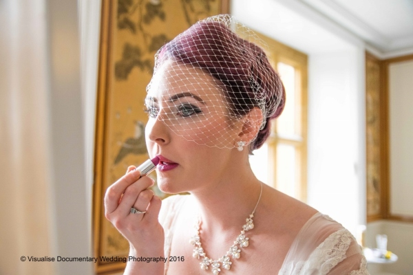 the bride putting on lip stick before leaving for the wedding ceremony