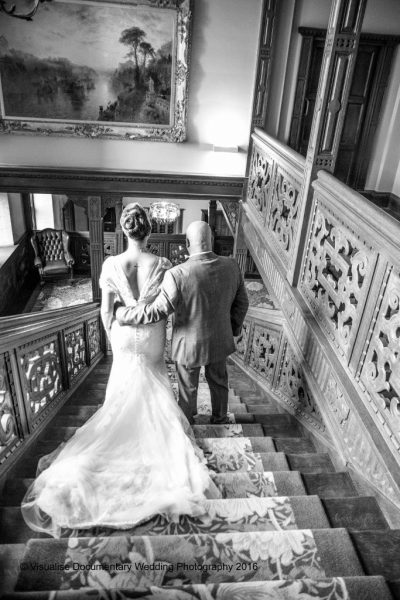 the bride and her father walk down the ornate staircase