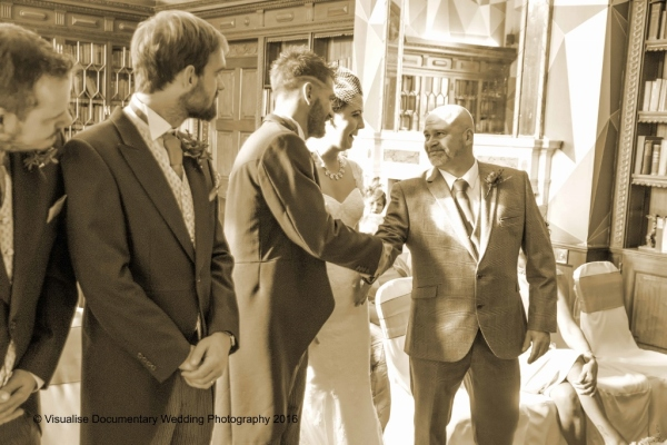 the groom and father of the bride shake hands at the start of the wedding ceremony