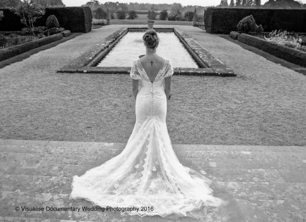 the bride stands and looks out onto the pond and gardens