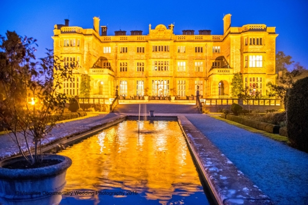 Eynhsam Hall lit up at night in orange colours with blue night sky
