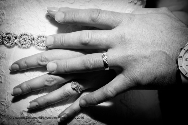 the bride and grooms hands crossed showing there wedding rings