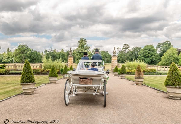 bride and groom in a horse and carriage at eynsham hall
