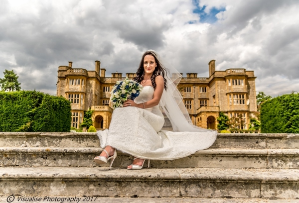a bride sat on the steps of eynsham hall