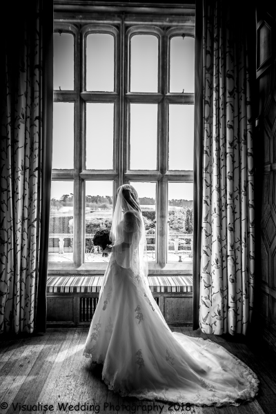 the bride at Eynsham hall looking through the window.