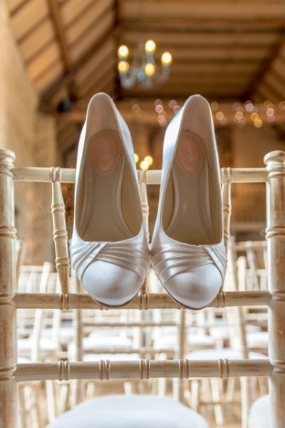 the brides wedding shoes on a chair