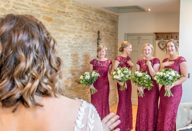 the bridesmaids first look at the beaming bride at The  Great Barn Aynho