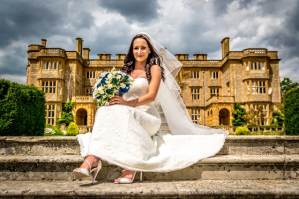Eynsham Hall wedding venue and the bride sitting on the steps
