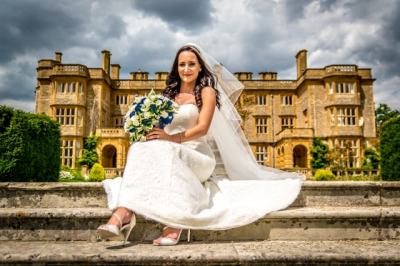 The bride sitting on steps outside her wedding venue , Wedding Photographers in Oxfordshire Eynsham hall wedding photography