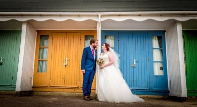 The bride and groom outside the beach huts in Bournemouth , Beach and Destination Wedding Photographer