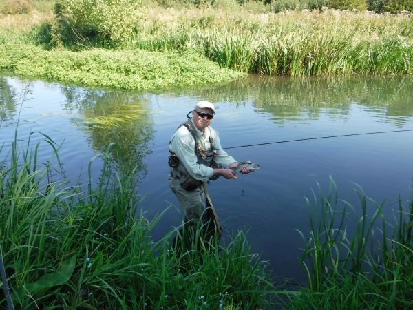 Fly fisherman with grayling from the river Avon