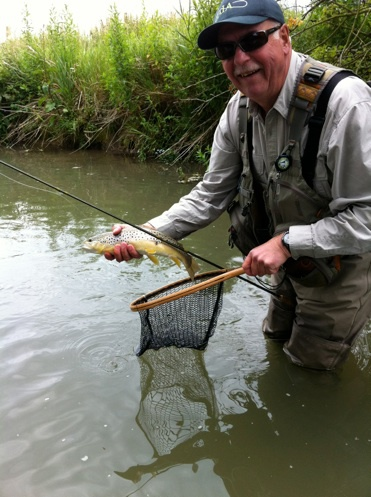 Happy fly fisherman with a wild brown trout from the river Windrush