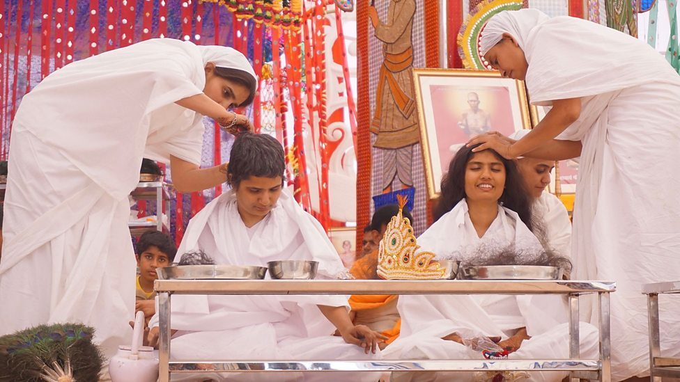 A Indian novice takes part in a hair plucking ceremony to become a Hindu nun