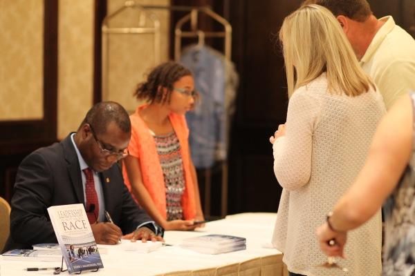 Dr. Malangwasira signing a book