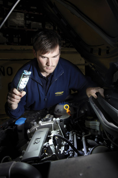 Mechanic shining Hamsar LED Flashlight onto vehicle engine
