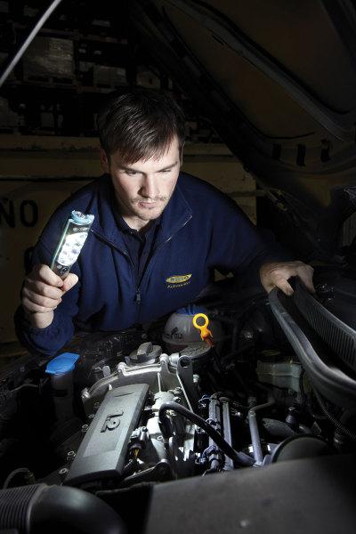 Mechanic shining Hamsar LED Flashlight onto vehicle engine