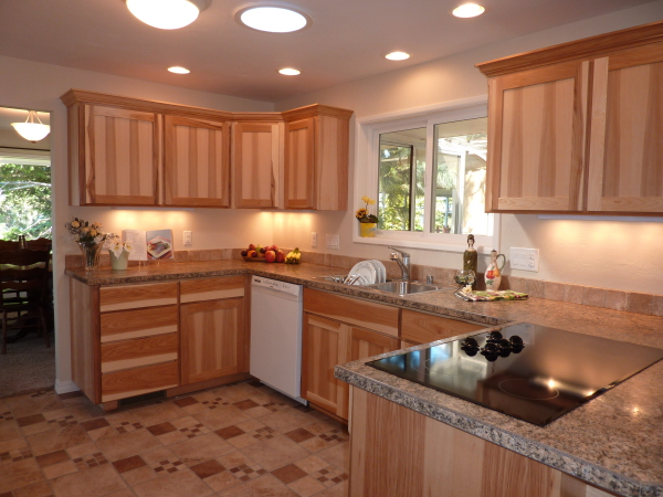 Natural Wood Shaker Style Kitchen with granite countertops, stainless steel double sink, inset black countertop electric range, under cabinet LED lighting and ceramic tile flooring.