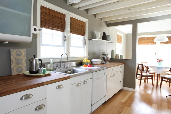 Vintage Kitchen with butcher block countertops, bamboo flooring, stainless steel sink with extended stainless steel cutting board.