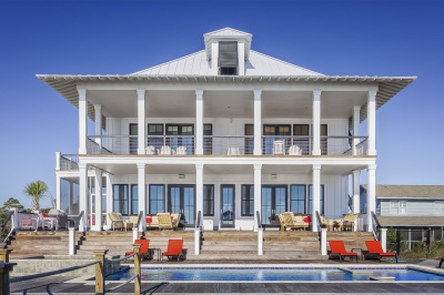White Coastal Home with Metal Roof, two story, back deck over looking pool