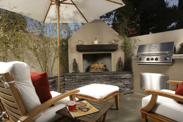 Cozy outdoor patio with stucco walls, corner fireplace with mantle and stone base, and built in stainless gas grill.