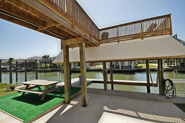 Boat dock with lift.  Balcony and railing.  Fish cleaning table and picnic area.
