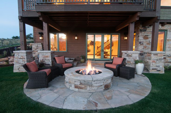 Outdoor fire pit with stone flooring, stone pit encasing all matching stone on exterior of home.