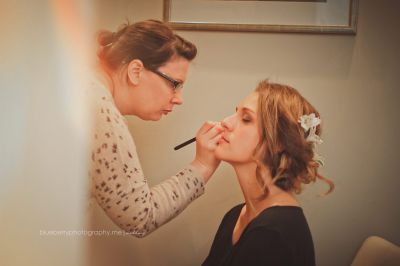 Nicola Louise Makeup applying the finishing touches to her bride on her wedding day ensuring her makeup is flawless and looking beautiful