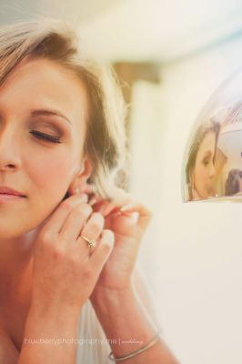 A thoughtful bride finishing off getting ready for her wedding day