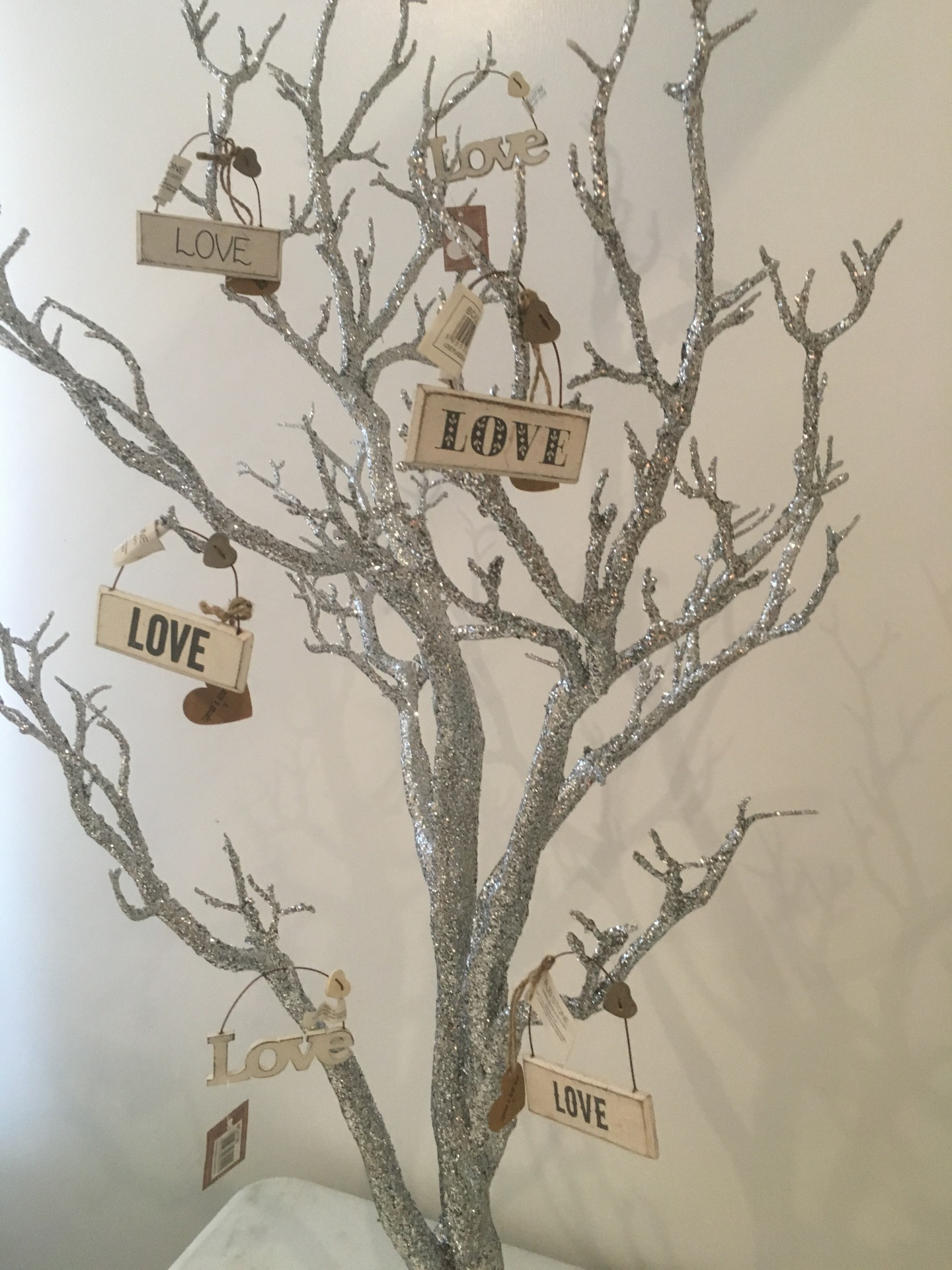 Manzanita trees in silver shown with hanging love decor