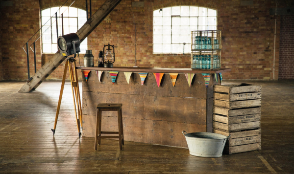 Rustic mobile bar made form pine and mahogany with vintage theatre light, storm lanterns and milk churns