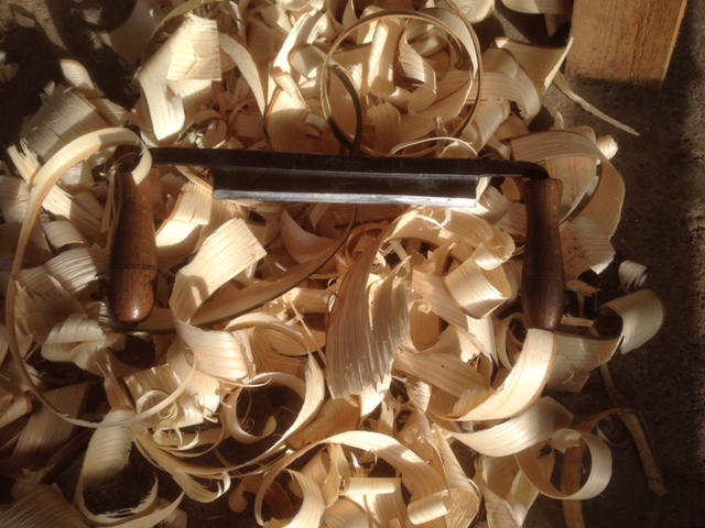 green woodworking tools, drawknife and wood shavings