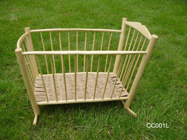 handcrafted rustic ash chair spindled doll's crib on grass background